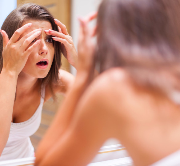 Young woman surprised to see herself in the mirror and notice imperfections on her skin