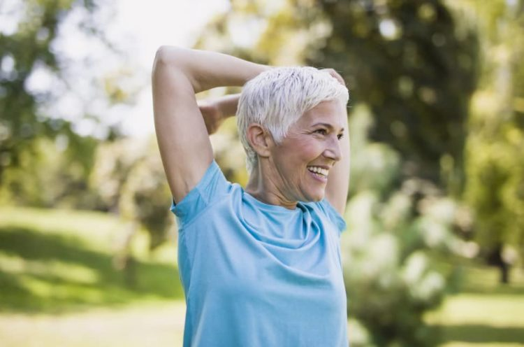 Elderly woman stretching outdoors to exercise.