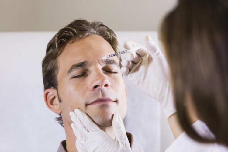 Man receiving dermatological treatment on his face.